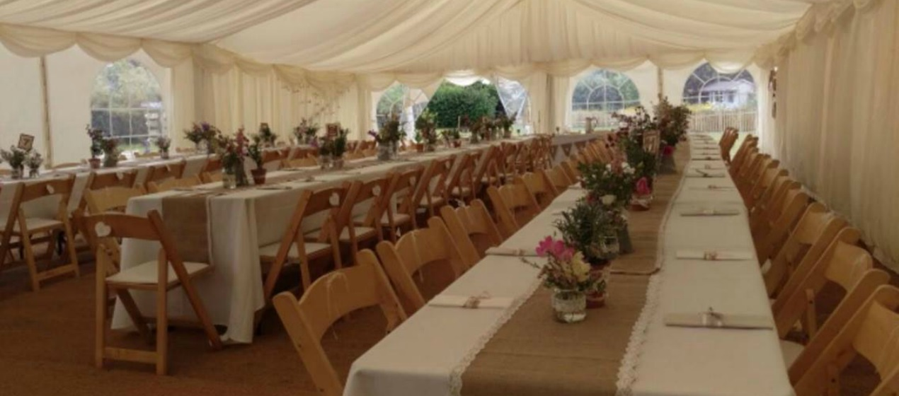 Wooden folding chairs with seat pads & trestle tables with white cloth